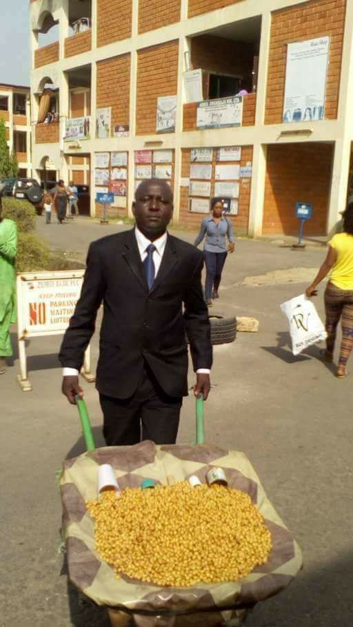 Photo of This Abuja man goes about selling his tiger nuts dressed in complete suit and tie
