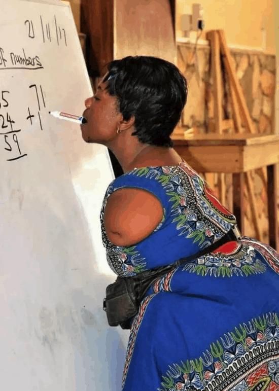 Photo of Armless mathematics teacher writing with her teeth goes viral