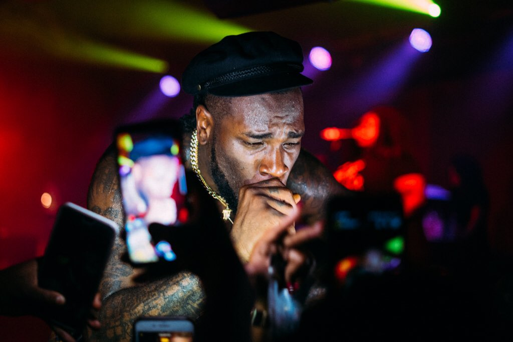 Burna Boy excited over lovely photos a fan took of him performing on stage