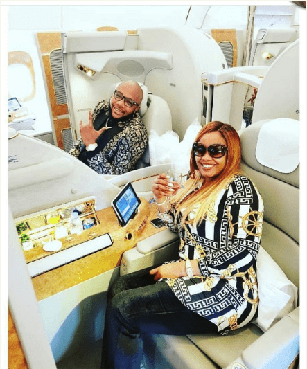 Photo of E-money and wife Juliet Okonkwo give each other a treat as they fly to Bangkok